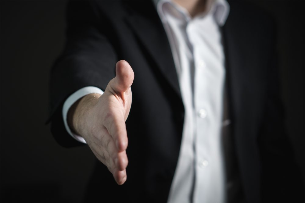 Point of view image of a suited man offering out his hand to shake as he offers you a graduate job because you have the right electronics career skills - an example would be networking for engineers.