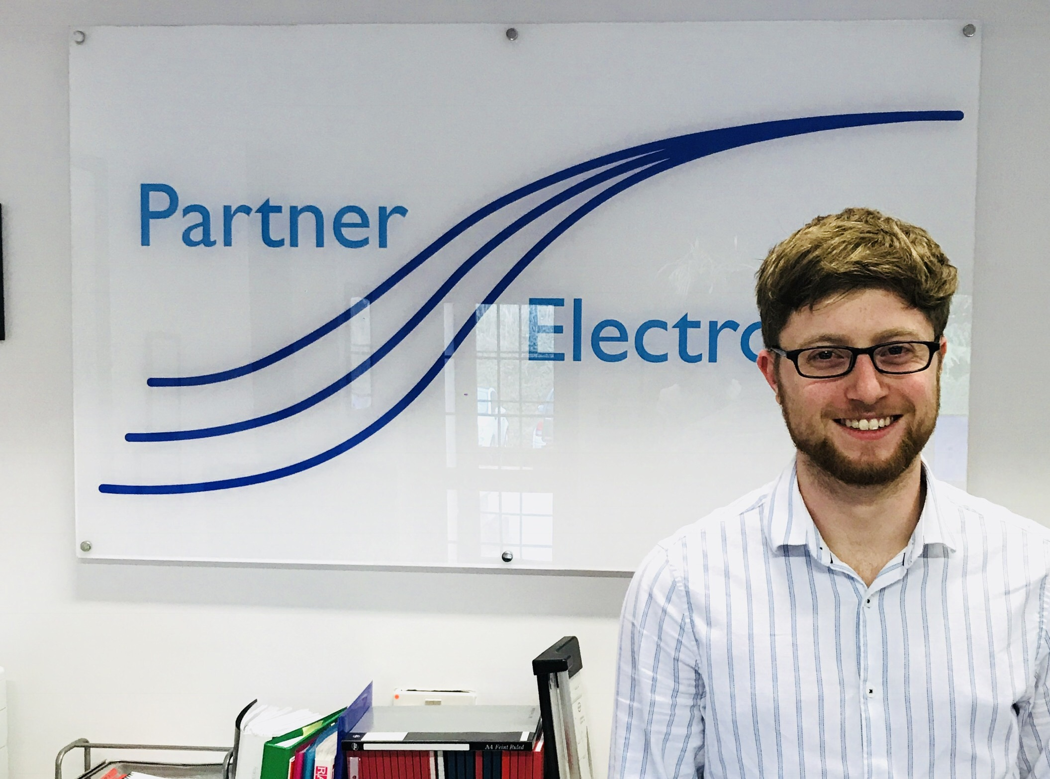 Pic of new graduate recruit Ryan Clark infront of our Partner Electronics sign