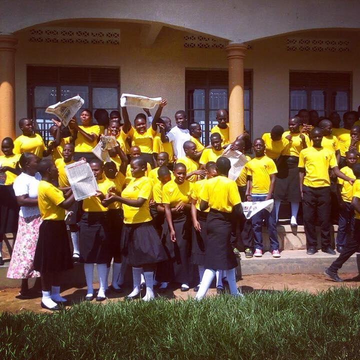 Secondary school students celebrate their exam success outside their school built by the charity Love iN aCTION